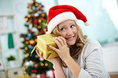 stock photo of guess  - Portrait of happy girl holding giftbox and guessing what is inside on Christmas evening - JPG