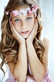 Portrait of beautiful little girl wearing floral wreath