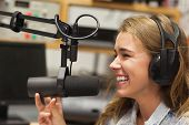 Laughing pretty radio host moderating sitting in studio at college