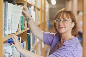 Mature female librarian taking a book off a shelf looking at camera