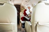 Bored Santa Claus sitting in private jet