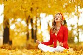 Yoga woman sitting in lotus position in autumn park