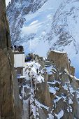 Tourists at the mountain top station of the Aiguille du Midi 3842 m in French Alps watching climbers