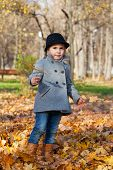 little girl in a coat walks in autumn park