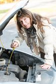 Beautiful woman checking engine oil level