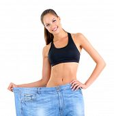 Slim girl in big jeans isolated on white
