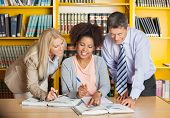 Mature college teachers assisting student with studies in library