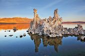The magic of Mono Lake. Outliers - bizarre limestone calcareous tufa formation reflected in the smooth water. Orange sunset