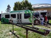 Golden Gate Transit Hybrid Bus On Display Behind Model Of Bridge