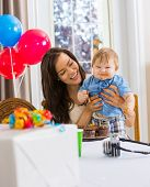Happy mother holding baby boy with messy hands covered with cake icing at birthday party