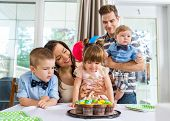 Happy family celebrating girl's birthday with cake on table at home