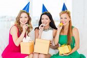 celebration, friends, bachelorette party, birthday concept - three smiling women wearing blue hats with gift boxes blowing favor horns