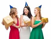 celebration, friends, bachelorette party, birthday concept - three smiling women wearing blue hats with gift boxes