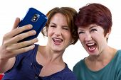 image of bff  - two female friend staking self portraits with a cell phone - JPG