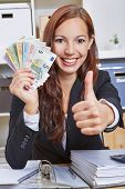 Happy smiling business woman in office with Euro money holding thumbs up