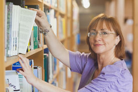 image of librarian  - Mature female librarian taking a book off a shelf looking at camera - JPG