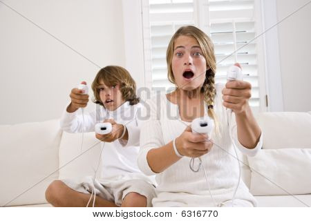 poster of Brother and sister playing video game on white sofa
