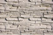 stock photo of tile cladding  - White cladding tiles imitating stones in sunny day - JPG