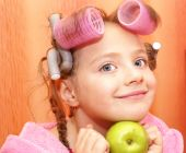 stock photo of housecoat  - Girl in a pink housecoat with curlers in the head and the apple of her face isolated on orange background - JPG