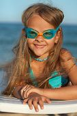 Little girl with swimming goggles sunbathing on the sea shore