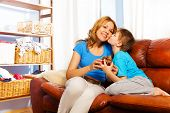 Boy kissing his mother giving gift on the sofa