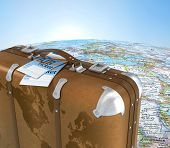 Old Suitcase With Air Ticket On Blurred World Map And Sky In Background