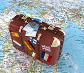 Old Suitcase With Air Ticket And Striples Flags On Blurred World Map In Background
