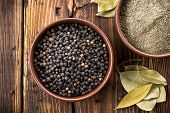 picture of peppercorns  - Black peppercorns in a bowl on a wooden table - JPG