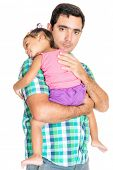 Serious hispanic father carrying his tired small daughter isolated on white