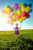 Happy little girl holding colorful balloons. Child playing on  green meadow. Smiling  kid. Portrait