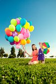 Cute little girl with mother colored balloons and rainbow umbrella holding  in the  park. Smiling ch