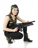 A beautiful teen girl wearing camouflage and combat boots, happily squatting and poised with her machine gun.  On a white background.