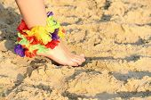 Foot On Sand With Flowers