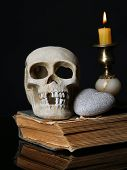 Skull and candle on old book isolated on black