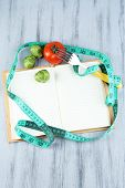 Book with measuring tape and vegetables on wooden background