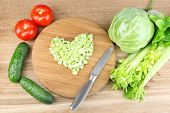 Heart shape of chopped celery  and fresh vegetables, on wooden background