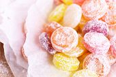 Sweet  multicolor candies on paper, close up