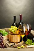 barrel, bottles and glasses of wine and ripe grapes on wooden table on grey background