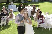 Mid Adult Bride And Groom In Garden Among Wedding Guests, Holding Wineglasses, Embracing