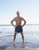 Full view of man standing with hands on hips at the beach