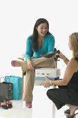 Sales clerk assisting teen girl buying shoes
