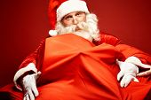 Portrait of Santa Claus embracing gigantic sack with gifts
