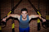 Young man doing exercises for arm muscles over brick wall and looking at camera