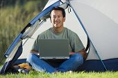 Portrait of man on laptop outside of tent