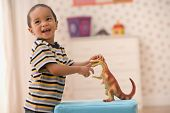 stock photo of dinosaur-eggs  - Young boy playing with toy dinosaur - JPG