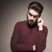 Picture of a attractive beard man, wearing a burgundy sweater, holding his hand to his ear, looking at the camera
