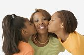 Daughters kissing their mothers' cheeks