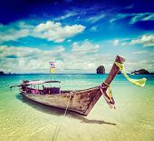 Vintage retro effect filtered hipster style travel image of long tail boat on tropical beach, Krabi, Thailand