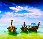Vintage retro effect filtered hipster style travel image of long tail boats on tropical beach, Krabi, Thailand