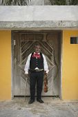 Senior Mariachi violinist standing in a doorway
